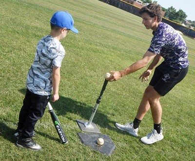 CHS sophomore John Orberson helps Ayden Stagner, a second-grader at Green County Primary School, as he practices batting.