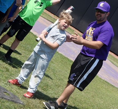CHS baseball head coach Blake Milby helps Campbellsville Elementary School first-grader Landry Brown as he practices his swing.