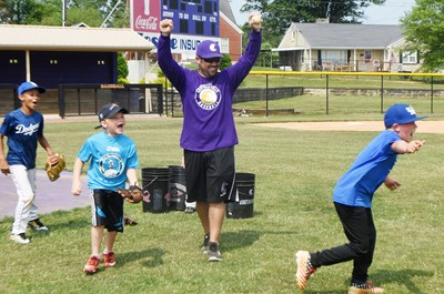 CHS baseball head coach Blake Milby and campers cheer as a camper catches a fly ball.