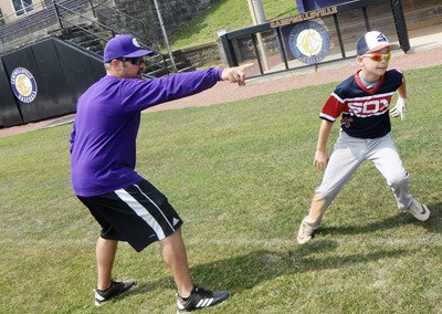 CHS baseball head coach Blake Milby helps Campbellsville Elementary School fifth-grader Cameron Estes as he learns to run the bases.