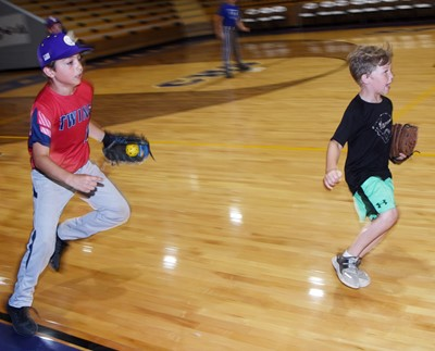 Campbellsville Elementary School fifth-grader Carson Mills, at left, fields the ball for an out as he and first-grader Landry Brown run for their turn to bat.