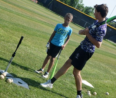 CHS sophomore John Orberson helps Campbellsville Elementary School second-grader Tyce Owens as he practices batting.