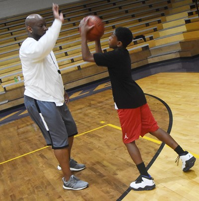 CHS boys' basketball head coach Anthony Epps guards Campbellsville Elementary School fifth-grader Jaron Johnson during a drill.