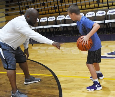 CHS boys' basketball head coach Anthony Epps instructs Campbellsville Middle School sixth-grader Cameron Estes during a drill.