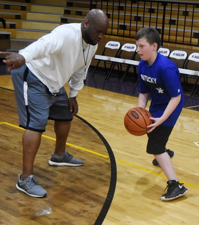 CHS boys' basketball head coach Anthony Epps instructs Campbellsville Middle School sixth-grader Izak Burress during a drill.
