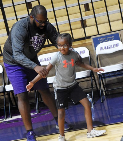 CHS boys' basketball assistant coach Will Griffin instructs his daughter, Campbellsville Elementary School first-grader Daya Griffin, during a drill.
