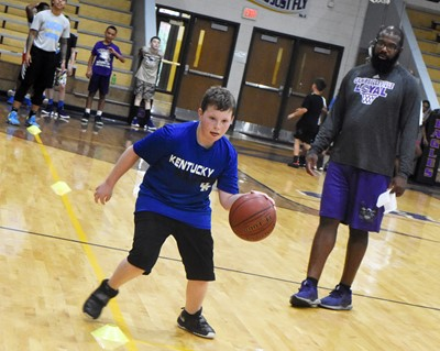 CHS boys' basketball assistant coach Will Griffin instructs Campbellsville Middle School sixth-grader Izak Burress during a drill.