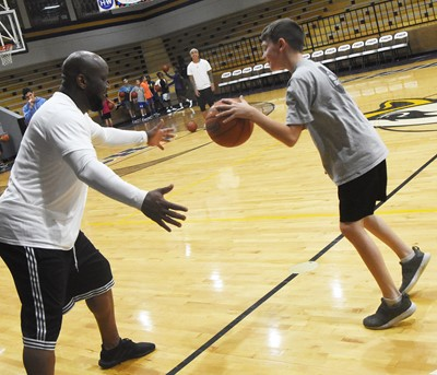 CHS boys' basketball head coach Anthony Epps instructs Campbellsville Elementary School fifth-grader Aidan Wilson during a drill.