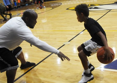 CHS boys' basketball head coach Anthony Epps instructs Campbellsville Elementary School fifth-grader Rajon Taylor during a drill.