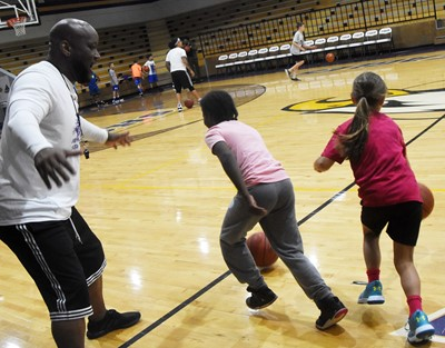 CHS boys' basketball head coach Anthony Epps instructs Campbellsville Elementary School fourth-grader Destini Gholston, at left, and Ila Loy during a drill.