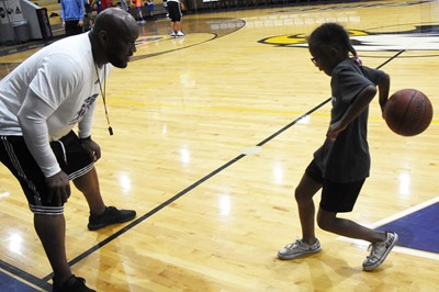 CHS boys' basketball head coach Anthony Epps instructs Campbellsville Elementary School first-grader Daya Griffin during a drill.