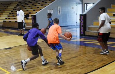CHS boys' basketball head coach Anthony Epps leads a dribbling drill with campers.