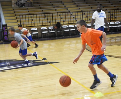 CHS boys' basketball head coach Anthony Epps leads a dribbling drill. In front is Campbellsville Middle School sixth-grader Keaton Hord.