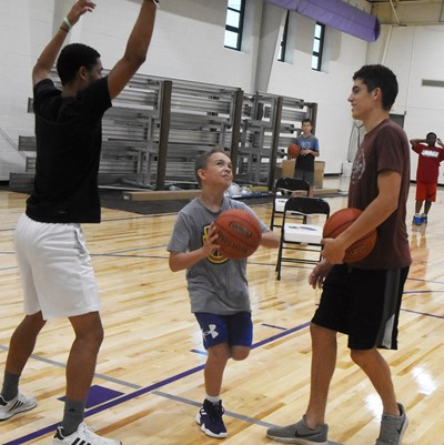 Campbellsville Middle School sixth-grader Cameron Estes shoots the ball, as he is guarded by CHS senior basketball player Mikael Vaught, at left, and junior player Kameron Smith.