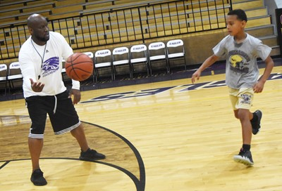CHS boys' basketball head coach Anthony Epps passes the ball to Campbellsville Elementary School fifth-grader Maddox Hawkins during a drill.