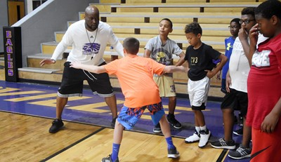 CHS boys' basketball head coach Anthony Epps instructs campers during a drill.