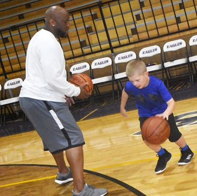 CHS boys' basketball head coach Anthony Epps guards Campbellsville Elementary School third-grader Grif Thomas during a drill.