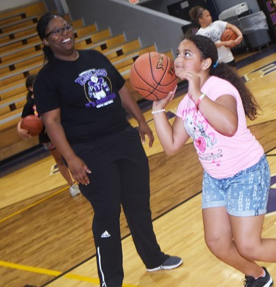 CHS girls' basketball assistant coach Tiarra Cecil helps Campbellsville Elementary School third-grader Maleigha Travis as she practices shooting.