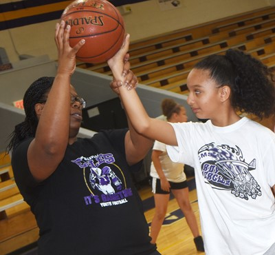 CHS girls' basketball assistant coach Tiarra Cecil helps Campbellsville Elementary School fifth-grader Alyssa Knezevic as she practices shooting.