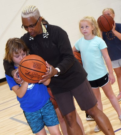 CHS girls' basketball assistant coach Debbie Gowdy-Smith helps Campbellsville Elementary School third-grader Mylee Bell as she shoots the ball.