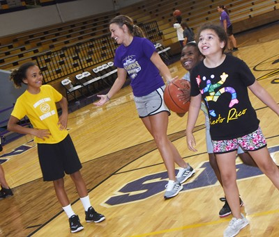 Campbellsville Middle School girls' basketball assistant coach LeeAnn Grider plays a game with campers, from left, Campbellsville Elementary School fourth-grader Braelyn Taylor and third-graders Destini Gholston and Ammarissa Nunez.