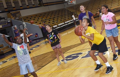 Campbellsville Middle School girls' basketball assistant coach LeeAnn Grider plays a game with campers, from left, Campbellsville Elementary School third-graders Destini Gholston and Ammarissa Nunez, fourth-grader Braelyn Taylor and third-grader Maleigha Travis.