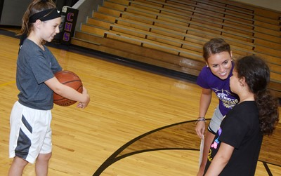 Campbellsville Middle School girls' basketball assistant coach LeeAnn Grider talks to Kennedy Deener, at left, and Campbellsville Elementary School third-grader Ammarissa Nunez as they play a game of one-on-one.