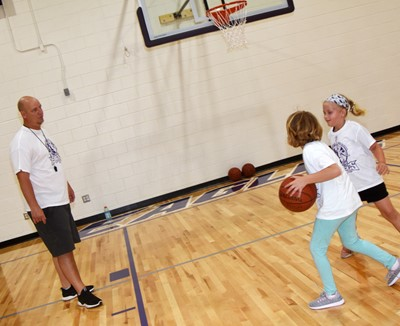 CHS girls' basketball head coach David Petett watches as Campbellsville Elementary School third-grader Mylee Bell, at left, takes on first-grader Remi Petett in a game of one-on-one.