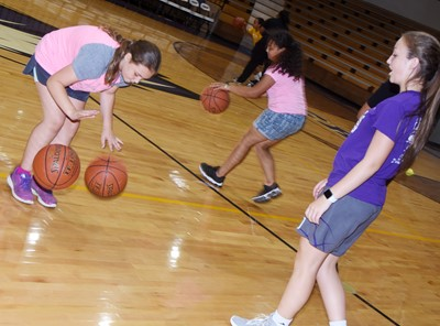 CHS freshman Lainey Watson helps Campbellsville Elementary School fifth-grader Kealey Mann practice her dribbling skills.