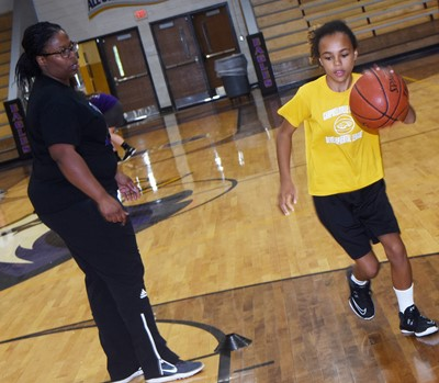 CHS girls' basketball assistant coach Tiarra Cecil helps Campbellsville Elementary School fourth-grader Braelyn Taylor as she practices shooting.