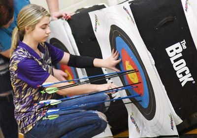 Campbellsville Middle School eighth-grader Braelyn Price pulls her arrows from her target.