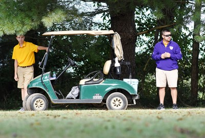 CHS golf coach Blake Milby and freshman player Bryce Newton watch as CHS golfers play.