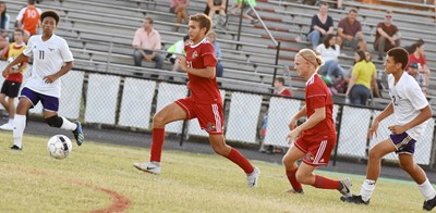 CHS junior Jastyn Shively, at left, and sophomore Brice Spaw run to the ball.