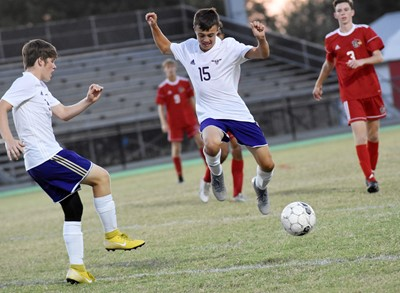 CHS sophomore Josh Lucas, at left, kicks the ball and freshman Chase Hord jumps.