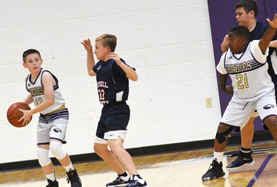 Campbellsville Elementary School fifth-grader Lanigan Price, at left, looks to pass as classmate Julian Smith blocks.