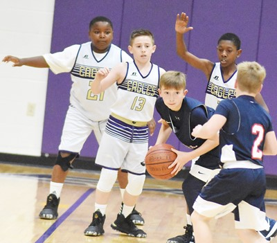 From left, Campbellsville Elementary School fifth-graders Julian Smith, Lanigan Price and Rajon Taylor play defense.