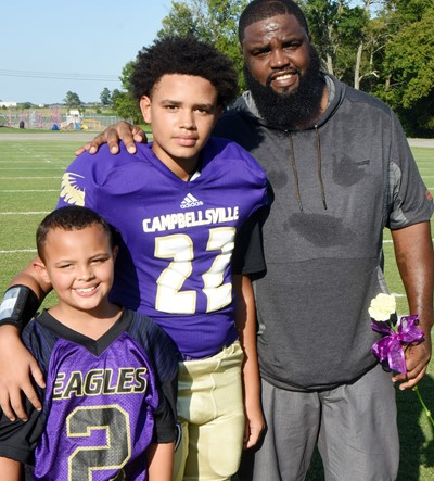 CMS eighth-grader Nasir Johnson is honored, with his father Ryan and brother Amir, who is a second-grader at Campbellsville Elementary School.