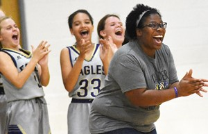CMS girls' basketball head coach Tiarra Cecil cheers with her players as they win.