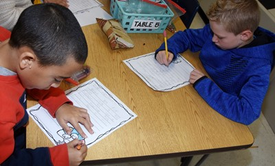 CES second-graders Cameron Carchio, at left, and Jackson Wright write their thankful letters.