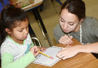 CES teacher Emily Andrew helps second-grader Amiiyah Nunez as she writes her thankful letter.