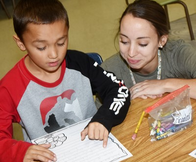 CES teacher Emily Andrew helps second-grader Chanler Mann as he writes his thankful letter.
