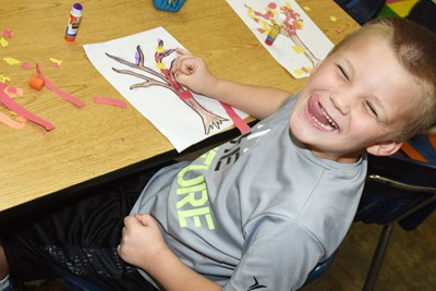 CES kindergartener Kaden Kessinger smiles as he makes his fall tree.