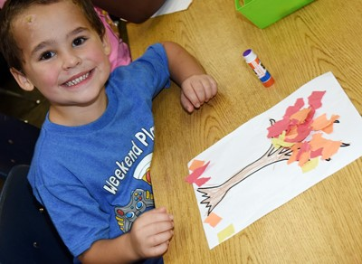 CES kindergartener Lukas Shofner smiles as he makes his fall tree.
