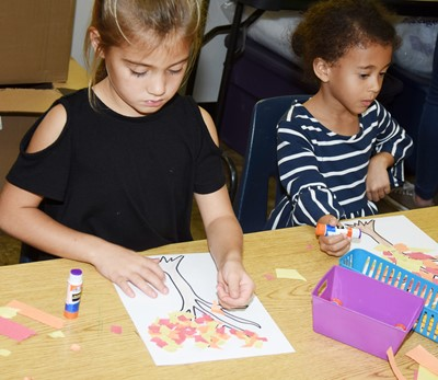 CES kindergarteners Blakely Gray, at left, and Riley Richardson make their fall trees.