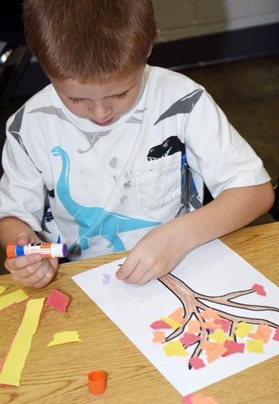 CES kindergartener Brian Daniels makes his fall tree.