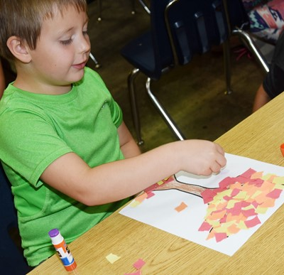 CES kindergartener Beckett Shelton makes his fall tree.