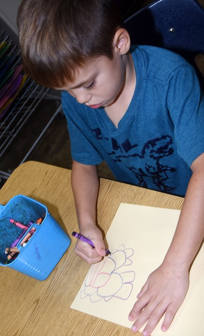 CES kindergartener Ryder Terry draws a picture of how he can be kind to others.