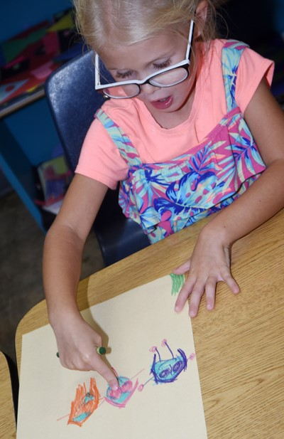 CES kindergartener Skyler Bray draws a picture of how she can be kind to others.