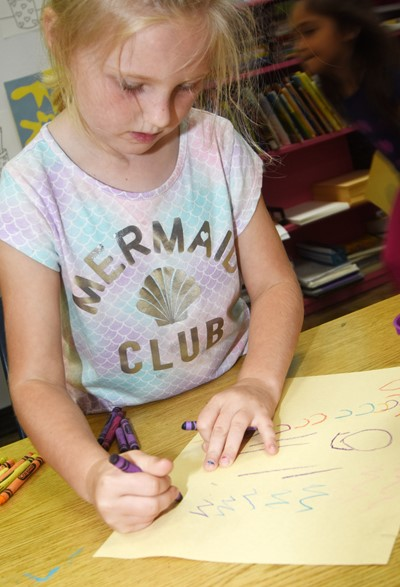 CES kindergartener Emma Armes draws a picture of how she can be kind to others.