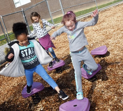 CES first-graders Aaliyah Jessie, at left, and Kylie Thompson play together on the playground.